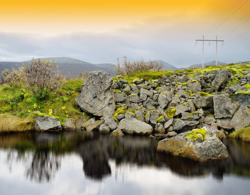 在路河反射附近的水平的生动的挪威橙色日落 库存图片