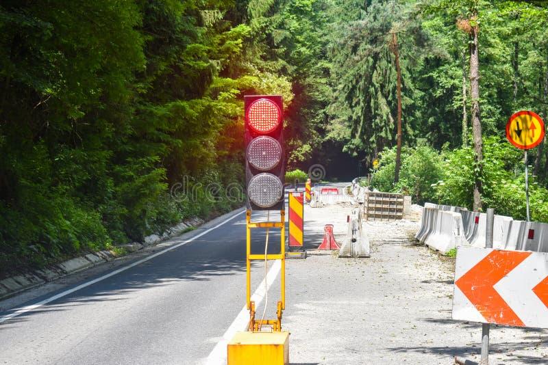 在路的一方式交通运动在修理下与红色红灯一起使用 在维护的损坏的路 库存图片