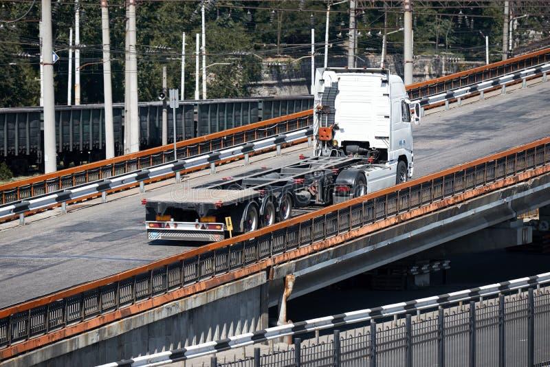 在路的一辆白色卡车乘坐在桥梁、工业基础设施、货物运输、交付和运输概念 库存照片