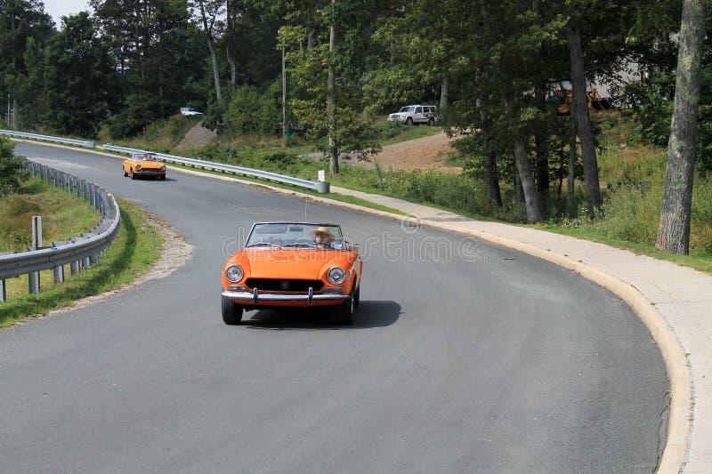 在路的两辆经典橙色意大利跑车 免版税库存照片