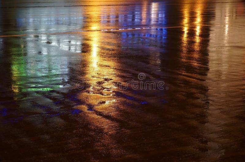在路的五颜六色的水反射 在水坑反映的城市光 库存照片