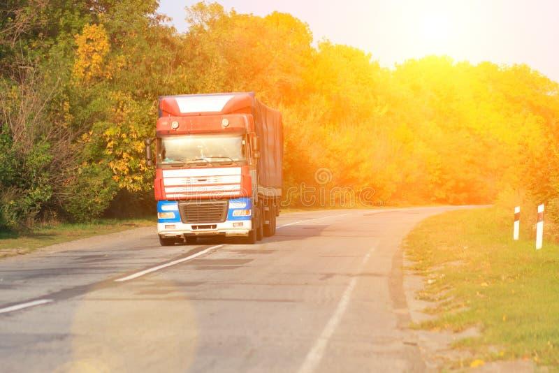 在路的卡车有白色空白的容器、运输、交付和货物运输概念的在日落 免版税图库摄影