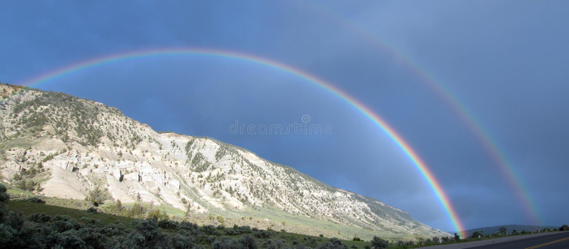 在路的双重彩虹向马默斯斯普林斯在黄石国家公园在怀俄明美国 库存照片