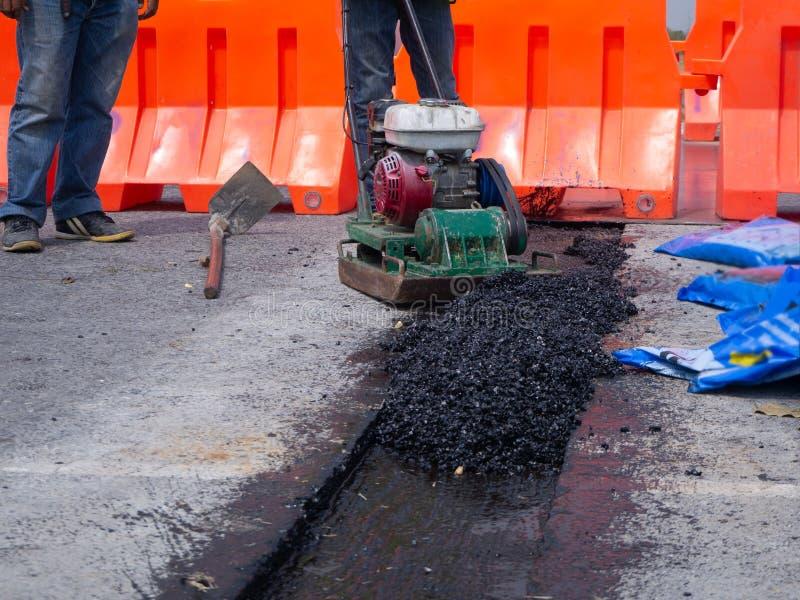 在路的工作者用途振动的板材压紧机变紧密的沥青 免版税库存图片