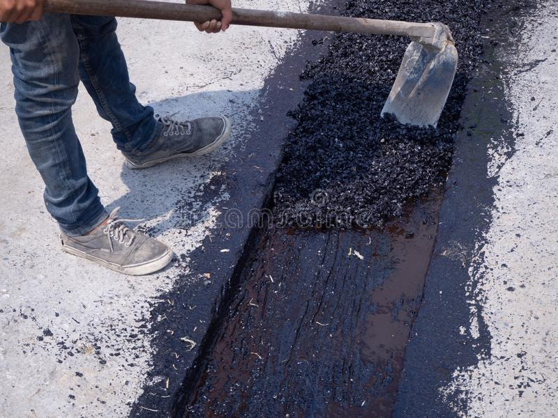 在路的工作者用途振动的板材压紧机变紧密的沥青 免版税图库摄影