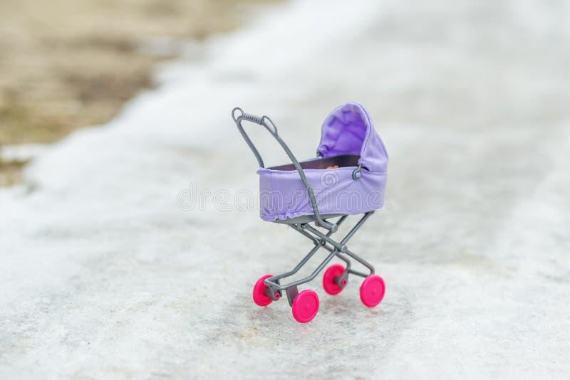在路的微小的玩具婴儿推车 童年,比赛,冬天的概念 库存照片