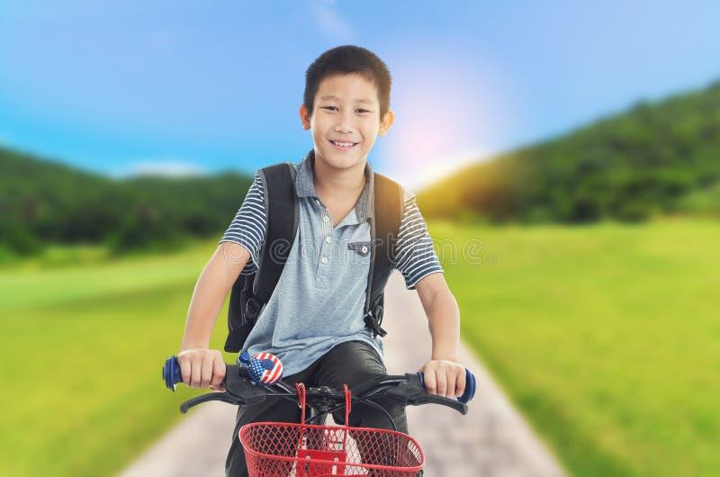 在路的愉快的亚洲男孩骑马自行车 免版税库存图片