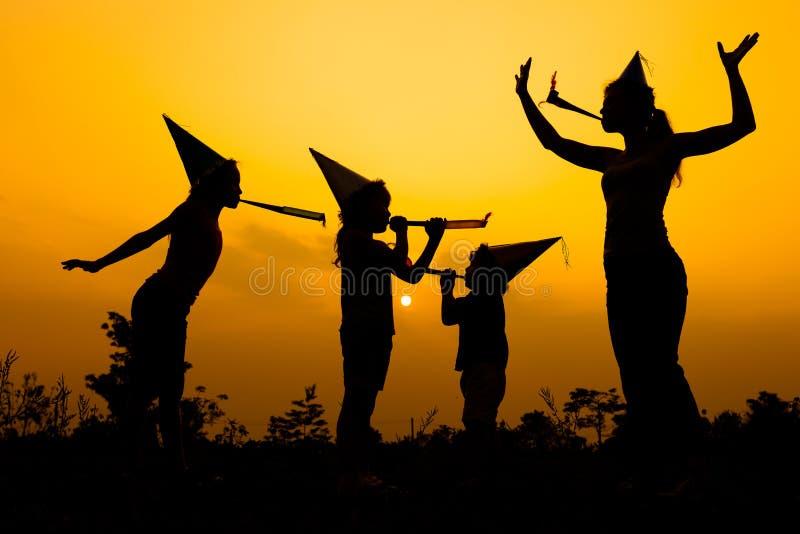 在路的愉快的家庭跳舞在日落时间 免版税库存图片