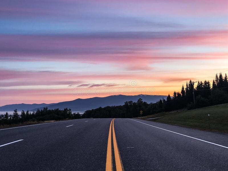 在路的日出向白色山 免版税库存照片