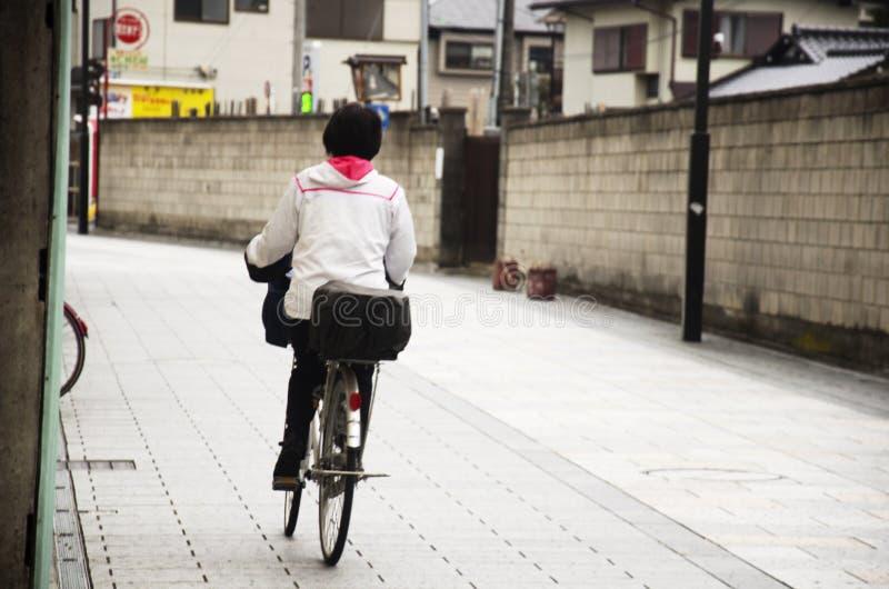 在路的日本妇女骑马自行车在埼玉,日本 免版税库存图片