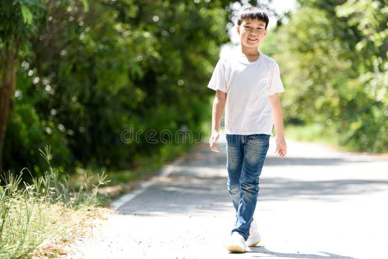 在路的男孩步行 免版税库存照片