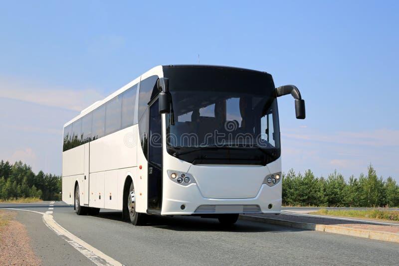 在路的白色公共汽车 免版税库存照片