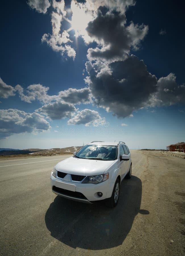 在路的白色汽车通过山 库存照片