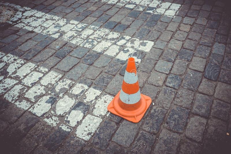 在路的老橙色交通锥体 免版税库存图片