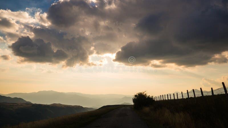 在路的运动在晚上在乡下的多云天 库存图片