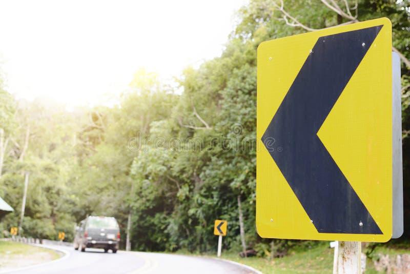 在路的黄色曲线交通标志 免版税库存图片