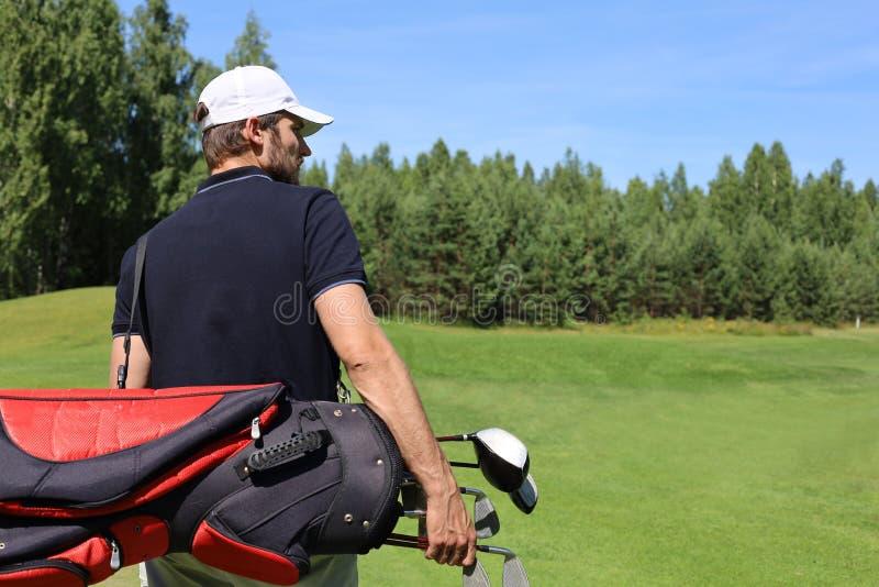 在路线的高尔夫球运动员走的和运载的袋子在夏天比赛打高尔夫球期间 免版税图库摄影