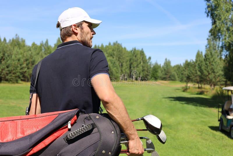 在路线的高尔夫球运动员走的和运载的袋子在夏天比赛打高尔夫球期间 免版税库存照片