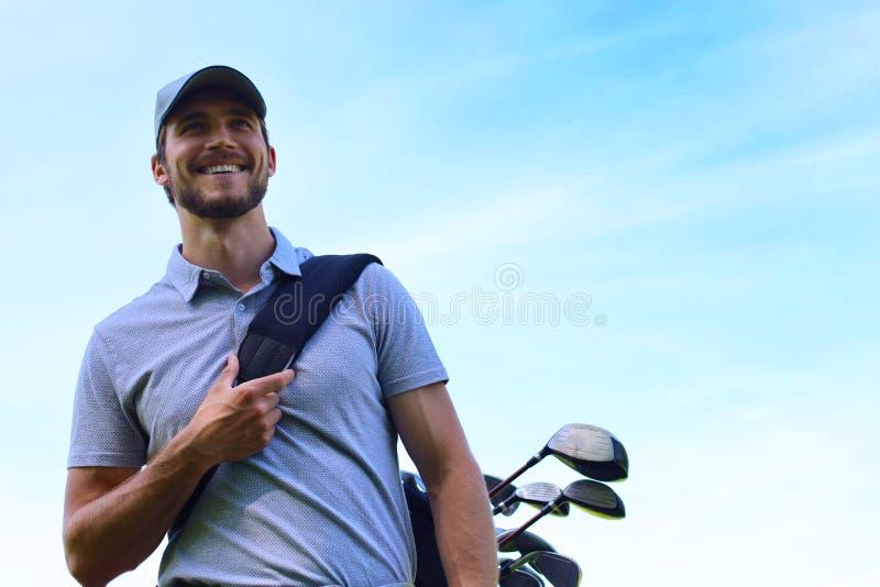 在路线的高尔夫球运动员走的和运载的袋子在夏天比赛打高尔夫球期间 免版税库存图片