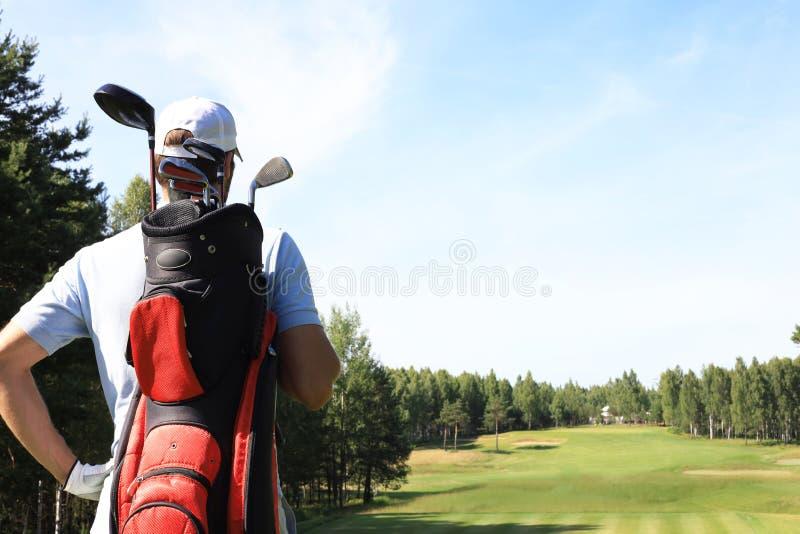 在路线的高尔夫球运动员走的和运载的袋子在夏天比赛打高尔夫球期间 库存照片