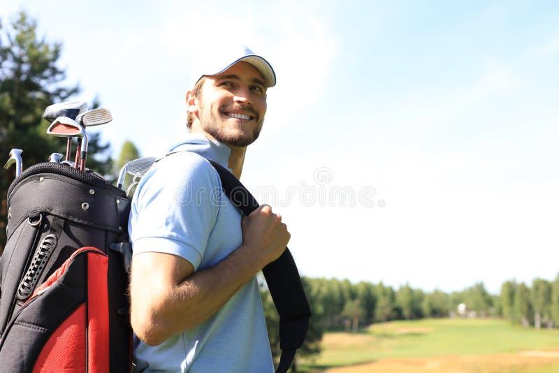 在路线的高尔夫球运动员走的和运载的袋子在夏天比赛打高尔夫球期间 库存图片