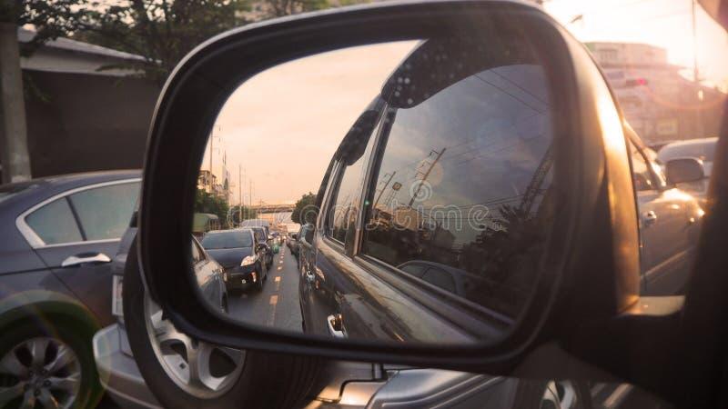 在路视图的交通堵塞通过有后边日落的后视镜汽车 免版税库存照片