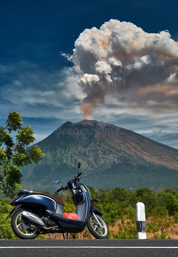 在路边缘的滑行车身分有在背景的阿贡火山火山剧烈的爆发的 库存图片
