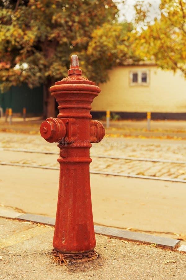 在路附近的老红火消防栓水管 免版税库存照片