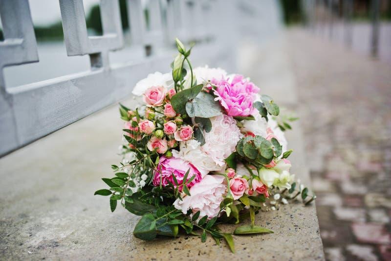 在路面的婚姻的美丽的玫瑰色花束 免版税库存照片
