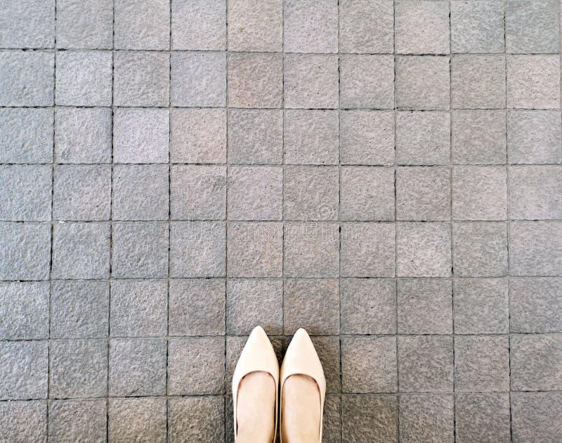 在路面背景,顶视图的高跟鞋 从上面看的脚和腿的Selfie女性 美好的时尚妇女身分 免版税图库摄影