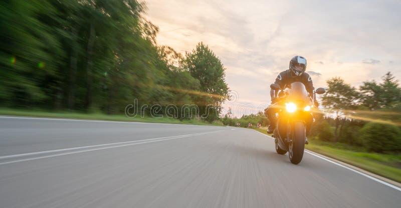在路骑马的摩托车 获得乘坐空的路的乐趣在摩托车游览/旅途 免版税库存照片