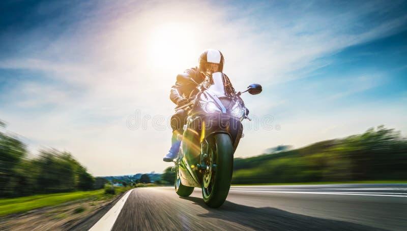 在路骑马的摩托车 获得乘坐空的路o的乐趣 库存照片
