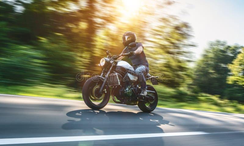 在路骑马的摩托车 获得乘坐空的路o的乐趣 免版税库存照片