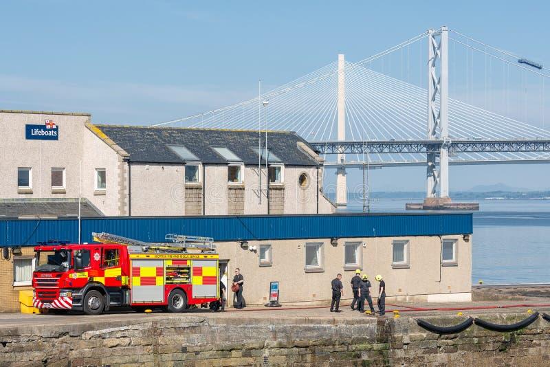 在跳船救生艇的火旅团锻炼在路桥梁附近驻防 免版税库存照片