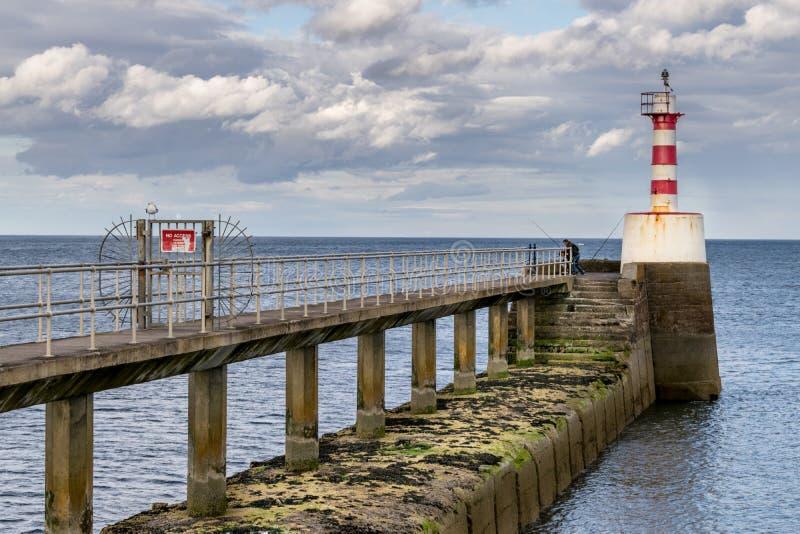 在跳船的末端的一座小红色和白色灯塔 免版税图库摄影