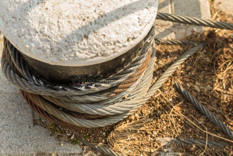 在跳船的码头特写镜头基地设计的背景的一强有力的金属缆绳包裹的石垫座 图库摄影