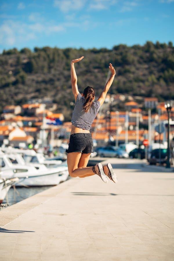 在跳跃在天空中的退出的愉快的妇女出于幸福 背景时钟概念查出时间假期墙壁白色 海边沿海假期兴奋 喜悦的妇女 免版税库存图片