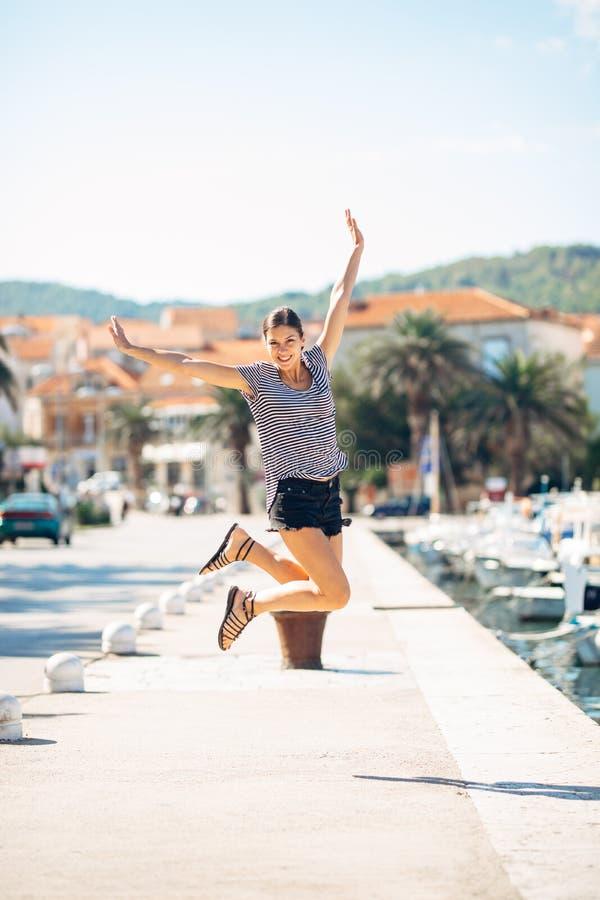 在跳跃在天空中的退出的愉快的妇女出于幸福 背景时钟概念查出时间假期墙壁白色 海边沿海假期兴奋 喜悦的妇女 库存照片