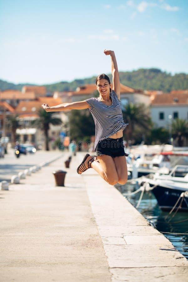 在跳跃在天空中的退出的愉快的妇女出于幸福 背景时钟概念查出时间假期墙壁白色 海边沿海假期兴奋 喜悦的妇女 免版税图库摄影