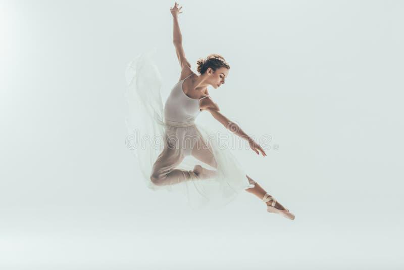 在跳跃在演播室的白色礼服的美丽的跳芭蕾舞者 免版税库存照片