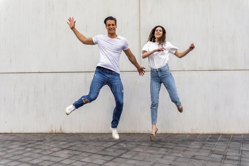 在跳跃对灰色墙壁的爱的愉快的夫妇 免版税库存照片
