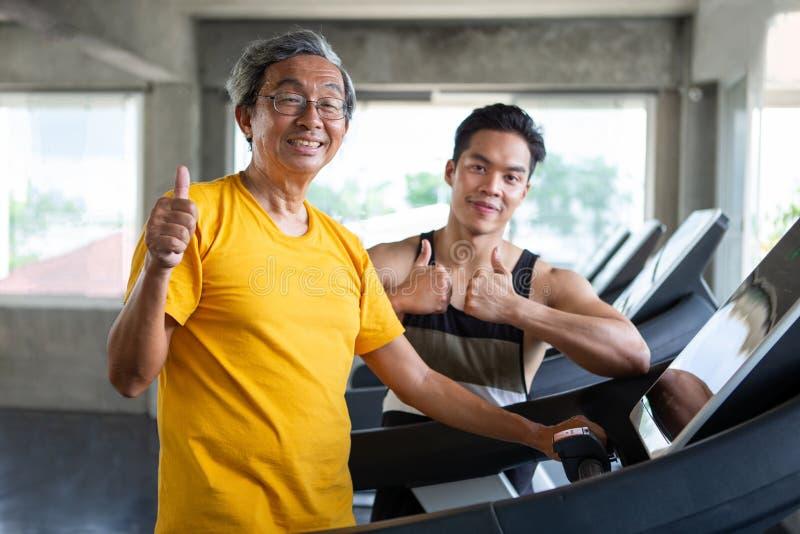 在踏车的亚洲老人走的锻炼有在健身健身房和展示赞许的个人教练员锻炼的 体育trainnig, 库存照片