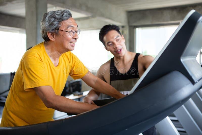 在踏车的亚洲老人走的锻炼有在健身健身房的个人教练员锻炼的 体育trainnig,退休,更旧, 免版税库存图片
