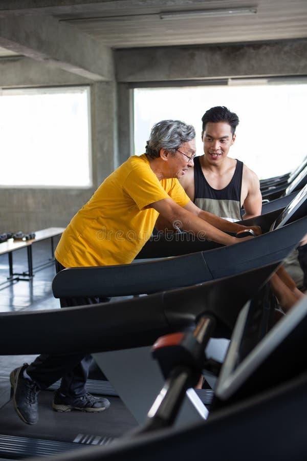 在踏车的亚洲老人走的锻炼有在健身健身房的个人教练员锻炼的 体育trainnig,退休,更旧, 免版税图库摄影