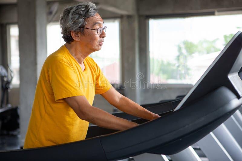 在踏车锻炼的亚洲老人走的锻炼在健身健身房 体育,trainnig,退休,更老,成熟,年长 库存图片
