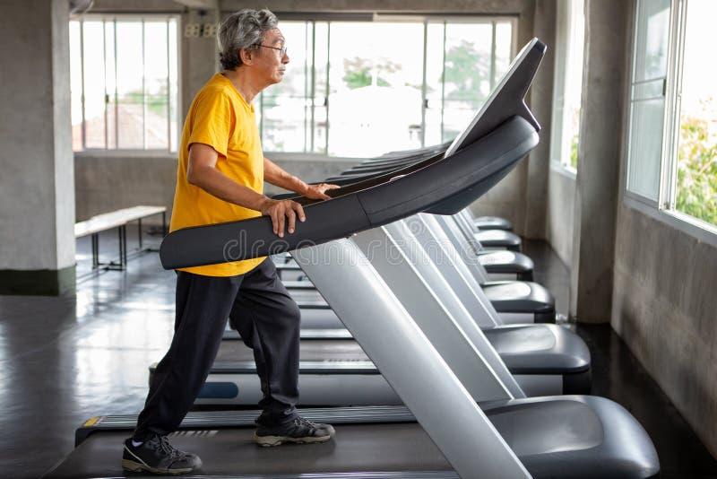 在踏车锻炼的亚洲老人走的锻炼在健身健身房 体育,trainnig,退休,更老,成熟,年长 免版税库存图片