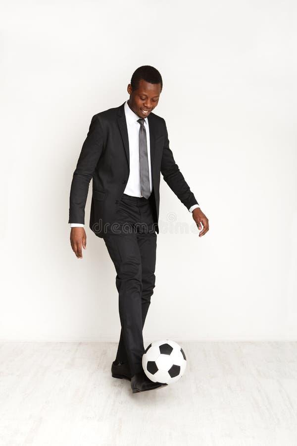 在踢橄榄球的衣服的严肃的商人 免版税库存照片