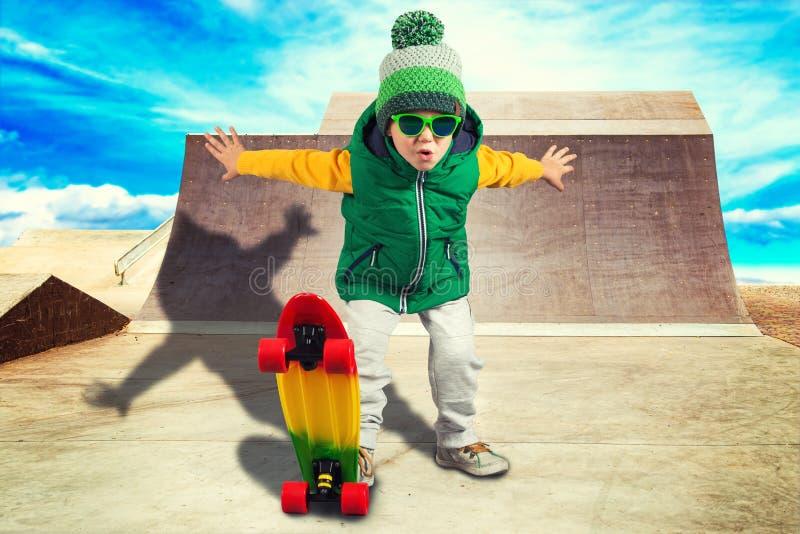 在踩滑板的陡峭的小山的小男孩骑马在冰鞋公园 极其体育运动 图库摄影