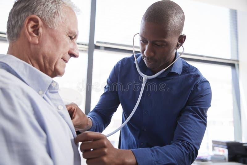在身体检查期间的Listening To Chest Of医生资深男性患者在办公室 免版税库存图片