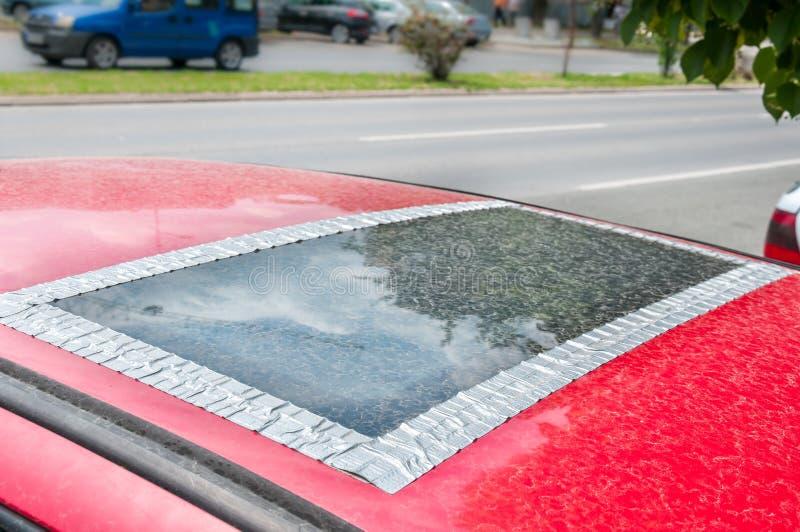 在车内部,损坏的玻璃屋顶窗口或遮阳篷顶在红色汽车胶合与胶带防止水来 免版税库存照片
